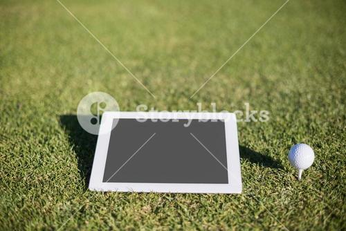 Close-up of golf ball on tee by digital tablet