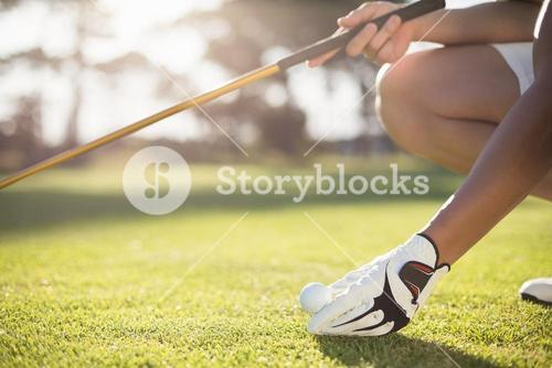 Cropped golfer man placing golf ball on tee