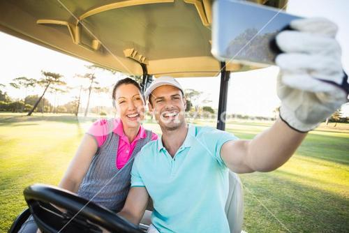 Golfer couple taking selfie while sitting in golf buggy