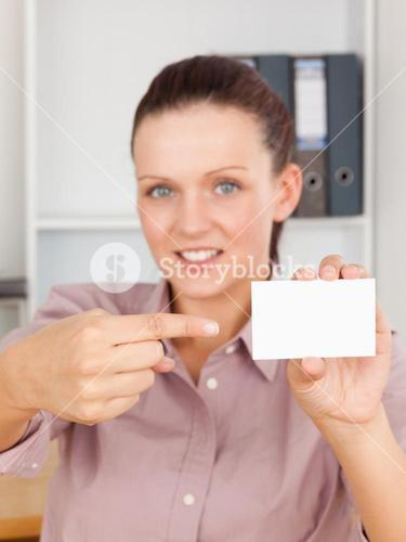Redhaired business woman pointing at a card