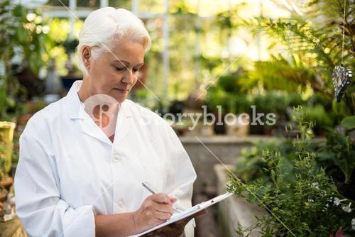 Female scientist writing in clipboard at greenhouse