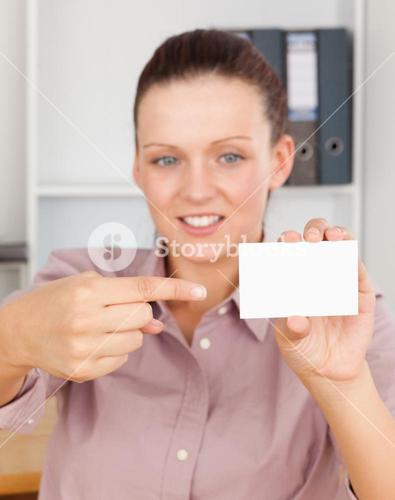 Gorgeous businesswoman pointing at a card