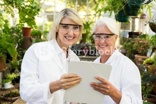 Female colleagues smiling while holding clipboard