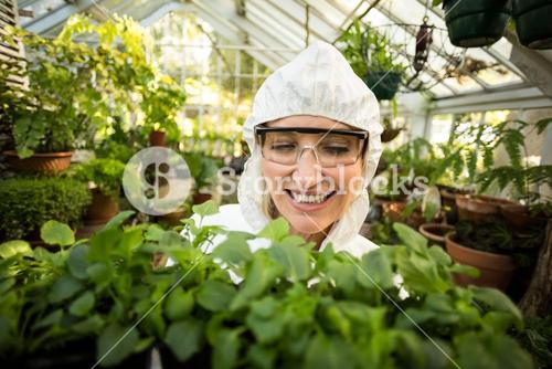 Female scientist smiling while holding plants