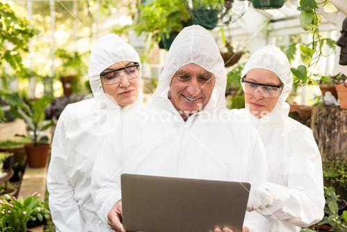 Male scientist discussing with colleagues over laptop