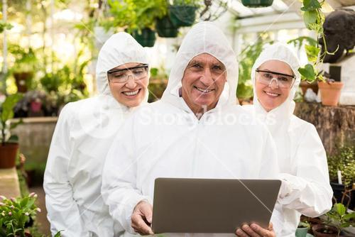 Happy coworkers in clean suit with laptop
