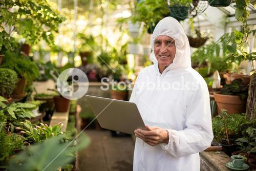 Happy male scientist using laptop at greenhouse