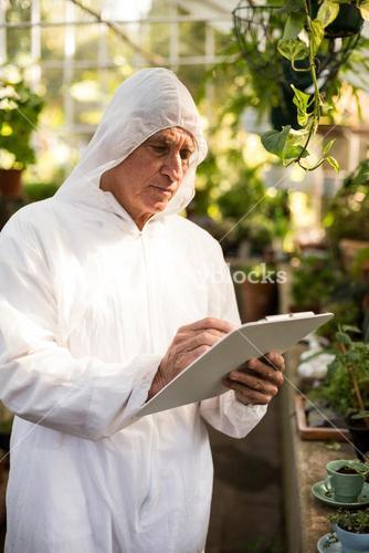 Male scientist writing on clipboard while examining plants