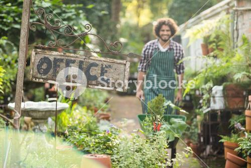 Office placard by plants while gardener in background