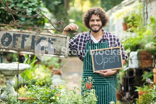 Male gardener holding open sign by office placard