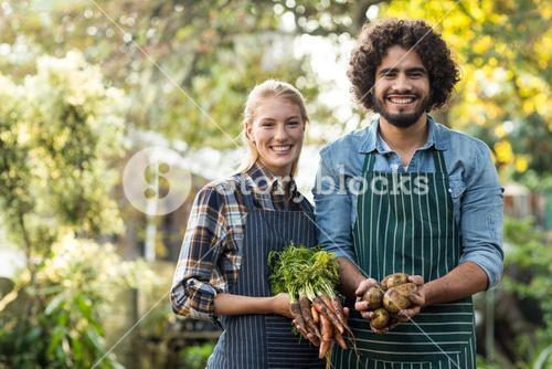 Happy coworkers holding harvested vegetables