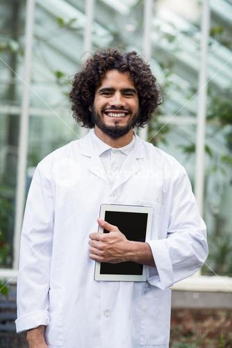 Male scientist holding digital tablet outside greenhouse