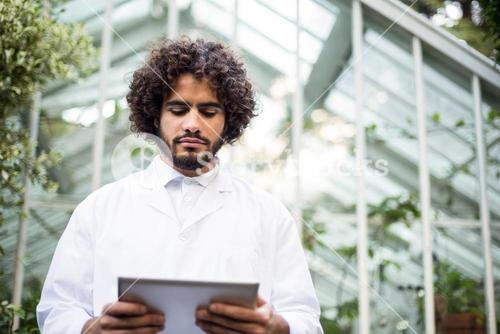 Male scientist using digital tablet outside greenhouse