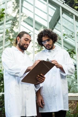 Male scientists discussing over clipboard