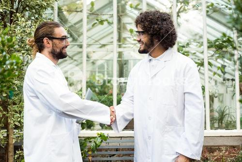 Male scientists handshaking outside greenhouse
