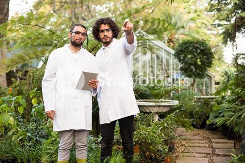 Male scientist pointing while coworker holding digital tablet