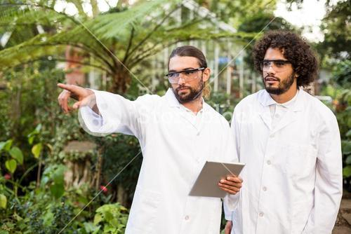 Male scientist pointing while standing by coworker