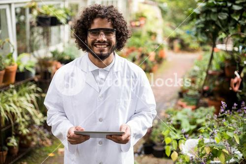 Confident male scientist holding digital tablet