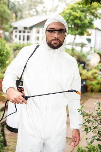 Portrait of male scientist spraying pesticides