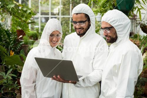 Scientists discussing over laptop