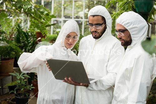 Scientists discussing over laptop at greenhouse