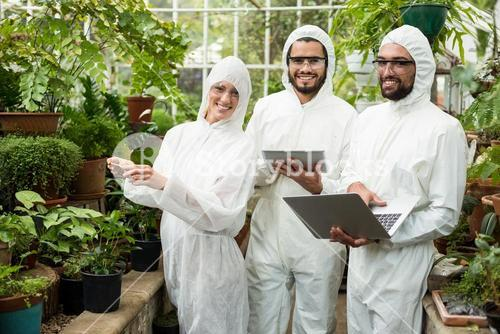 Happy scientists in clean suit using technologies