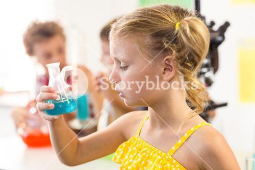 Close-up of girl looking at chemical