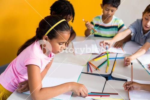Children with books and pencils on table
