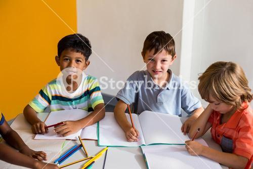 Cute boys with classmates in classroom