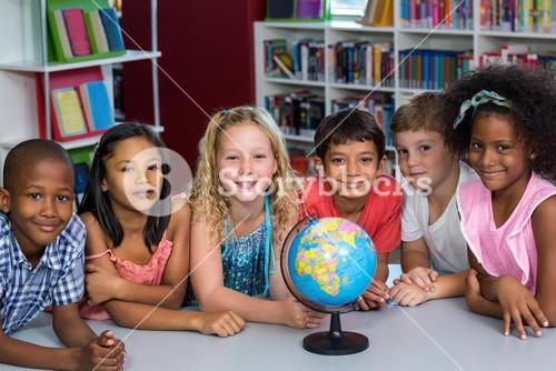 Smiling children with globe on table