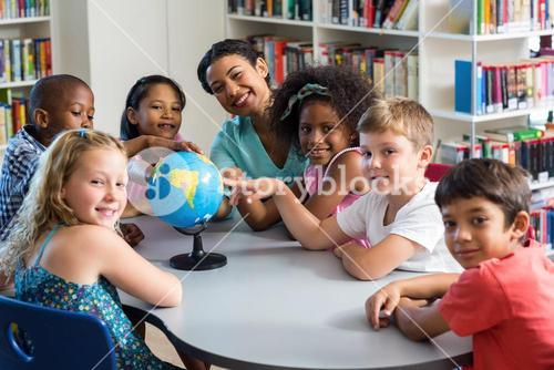 Female teacher and children with globe on table