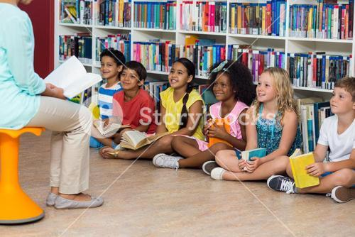 Teacher with smiling children in library