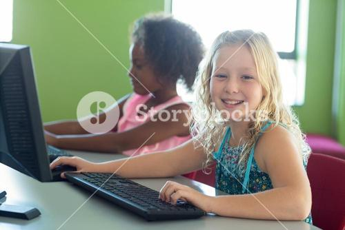 Happy girl with classmate using computers