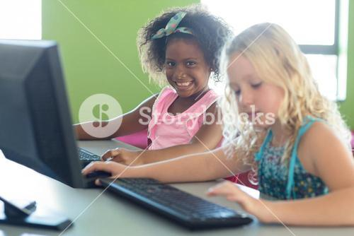 Smiling girl with classmate using computers