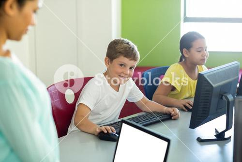 Boy with classmate and teacher using computers