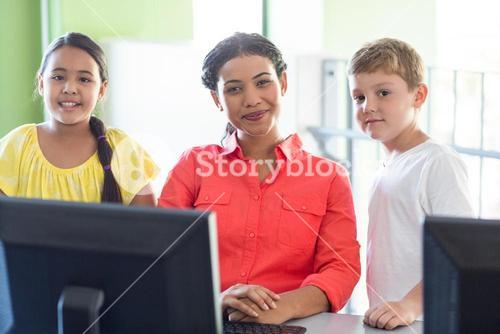 Female teacher with children in computer class