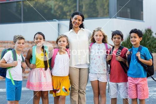 Teacher with children standing outside school