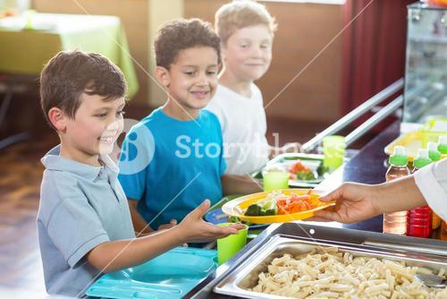 Cropped image of woman serving food to children