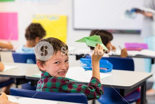 Cute boy holding paper airplane