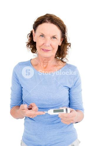 Portrait of smiling mature woman using blood glucose monitor