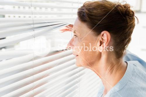 Mature woman looking through blinds