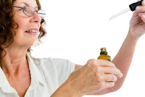 Close-up of mature woman holding dropper with medicine