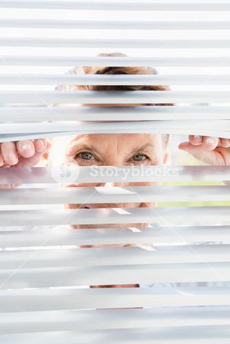 Portrait of mature woman looking through blinds