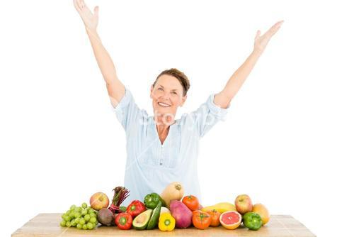 Smiling woman with arms raised while standing by fruits and vegetables at table