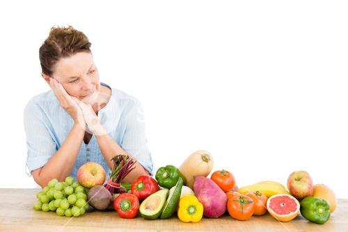 Thoughtful woman standing by fruits and vegetables