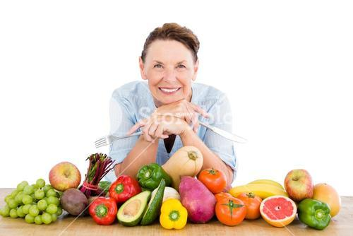 Portrait of smiling woman with fruits and vegetables at table