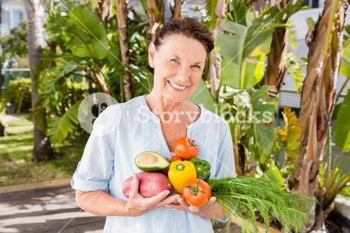 Cheerful woman holding fruits and vegetables