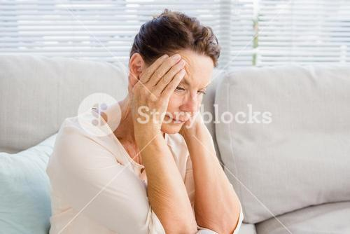 Woman with head in hands while sitting on sofa