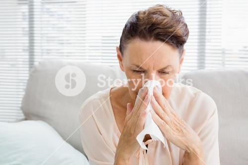 Mature woman with blowing nose