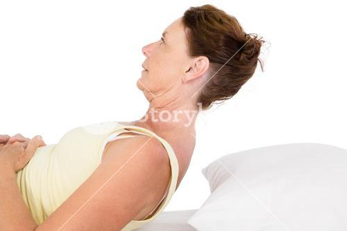 Mature woman exercising on bed